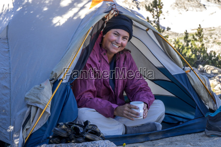 woman smiling while sitting in tent