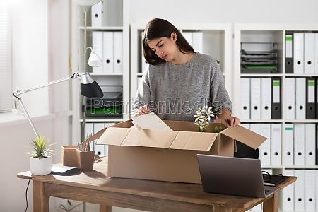 businesswoman packing her belongings in cardboard