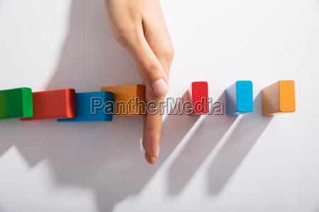 businessperson hand stopping colorful blocks from