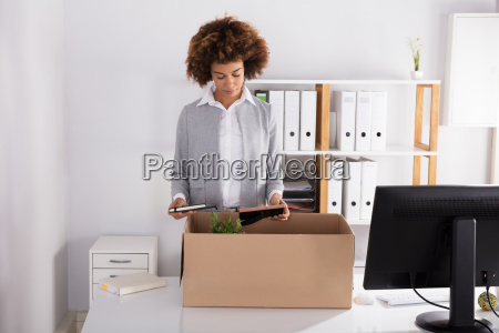 businesswoman, packing, her, belongings, in, cardboard - 23578536