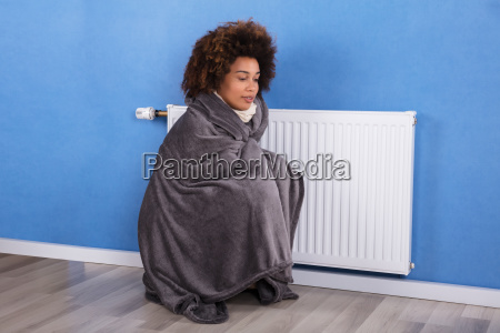 woman, sitting, near, heater, at, home - 23578518