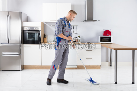 young, male, worker, mopping, floor - 23578430