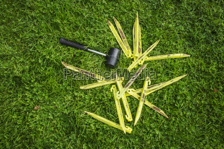 a mallet and yellow plastic pegs