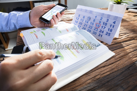 businessperson's, hand, planning, schedule, in, diary - 23584162