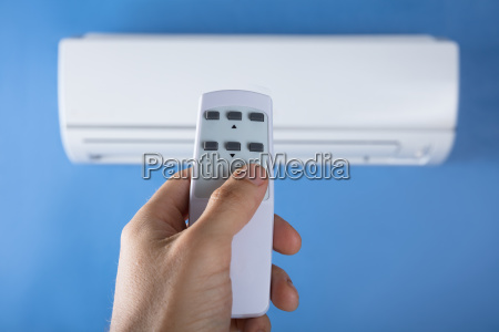 hand, adjusting, temperature, of, air, conditioner - 23584718
