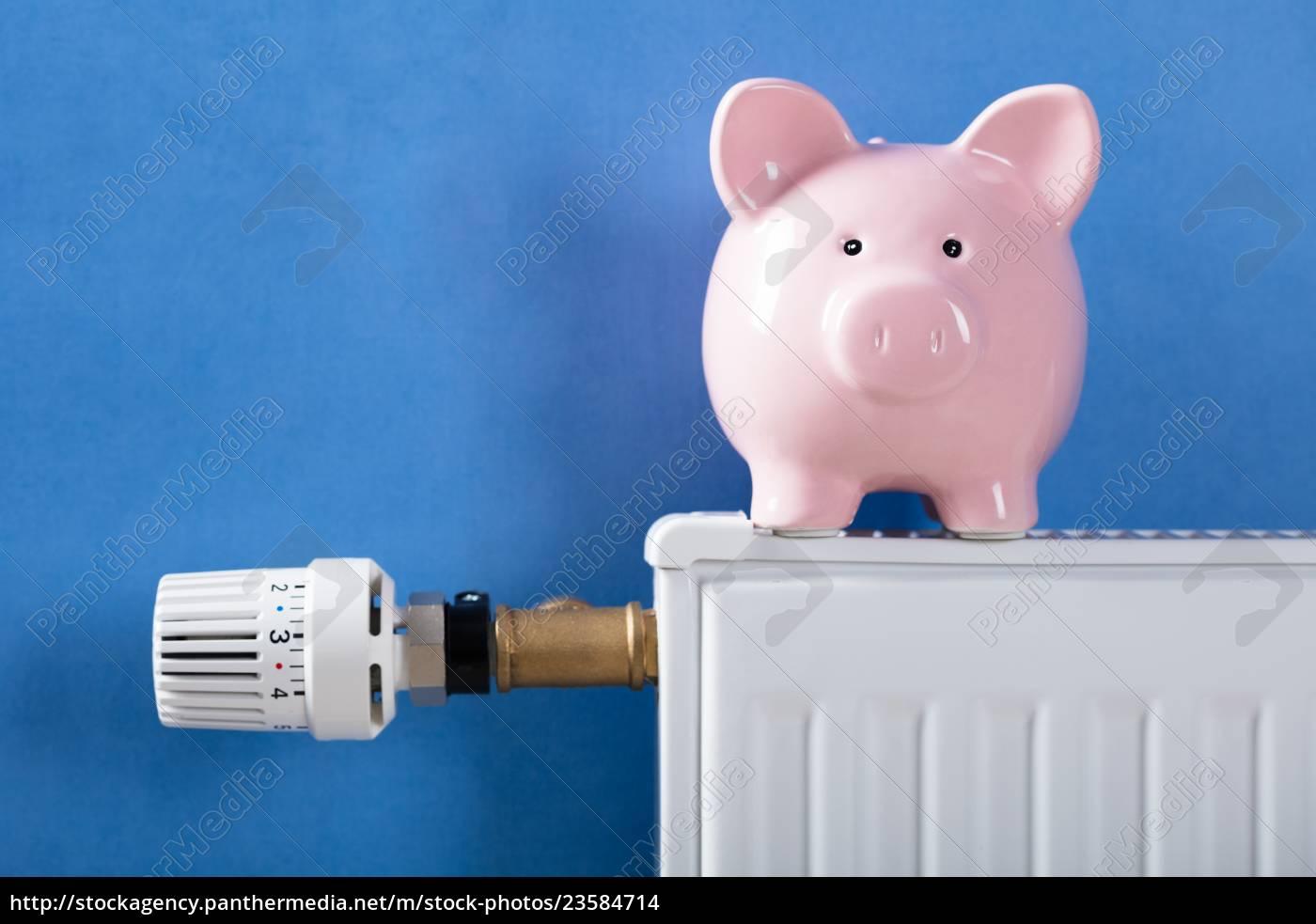 piggy, bank, on, heating, radiator - 23584714