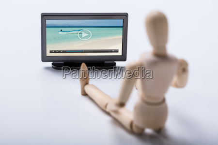 wooden, figure, watching, video, on, television - 23584106