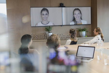 business people talking on monitors in