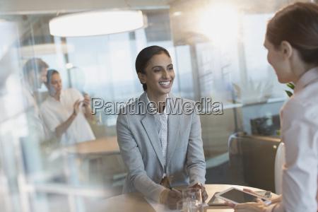 smiling businesswomen talking using digital tablet