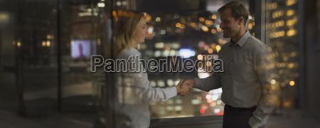 businessman and businesswoman handshaking in office