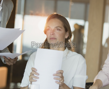 serious pensive businesswoman with paperwork looking