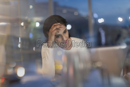 tired businesswoman working late at laptop