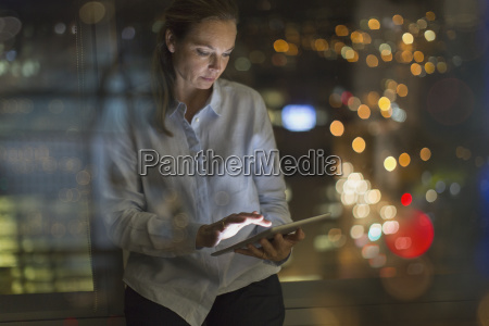 businesswoman working late at digital tablet
