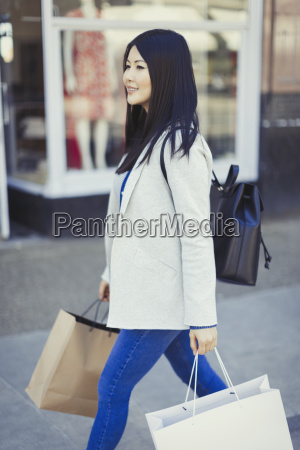 young woman walking along storefront with