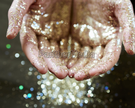 hands cupping gold glitter