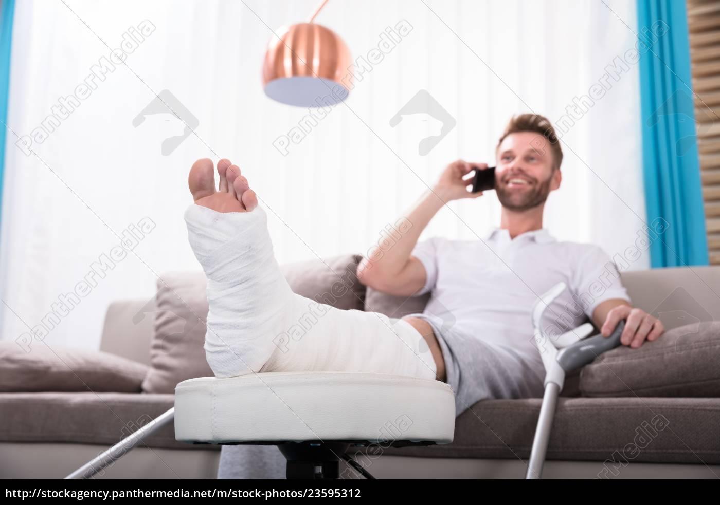 happy, young, man, with, broken, leg - 23595312