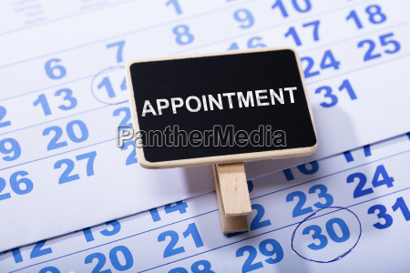 wooden miniature appointment placard on calendar