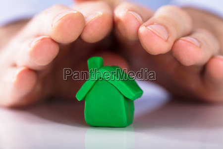 hands, protecting, the, green, clay, house - 23596036