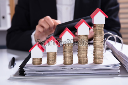businesswoman calculating invoice with house models