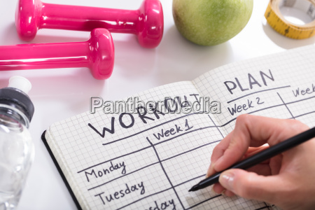 workout plan in notebook at wooden