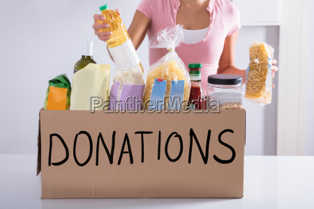 woman putting groceries in donation box