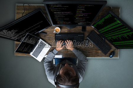 hacker hacking multiple computers on desk
