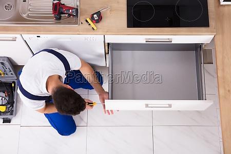carpenter fixing drawer in kitchen