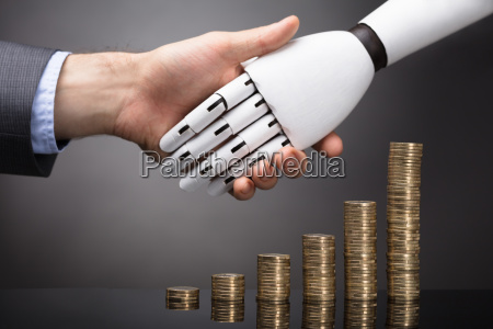 businessperson and robot shaking hands