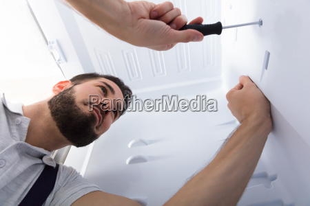 electrician, fixing, refrigerator, in, kitchen - 23597844