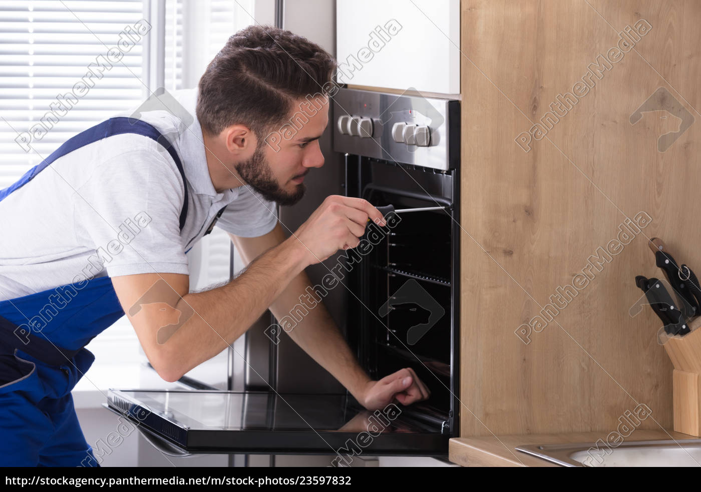 electrician, repairing, oven, with, screwdriver - 23597832