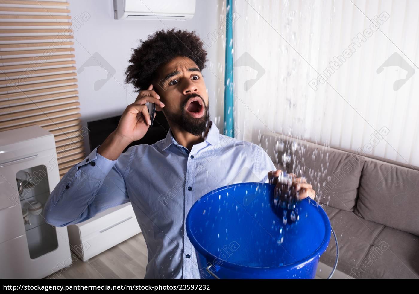 man, calling, plumber, while, leakage, water - 23597232