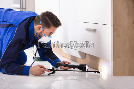 man, spraying, pesticide, in, kitchen - 23597826