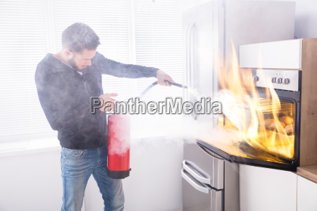 man, using, fire, extinguisher, to, stop - 23597724