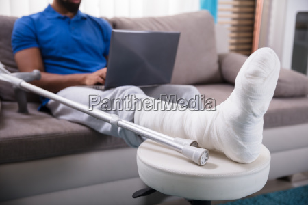 man, with, broken, leg, using, laptop - 23597170