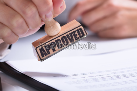 person, hands, using, stamper, on, document - 23597008