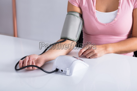 woman, measuring, her, blood, pressure - 23597042