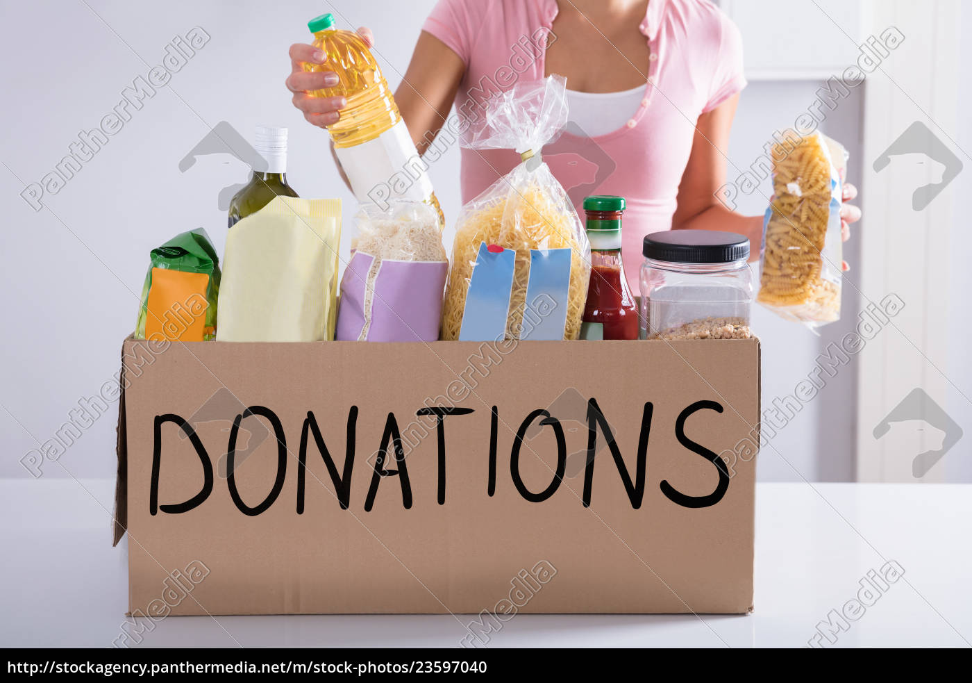 woman, putting, groceries, in, donation, box - 23597040