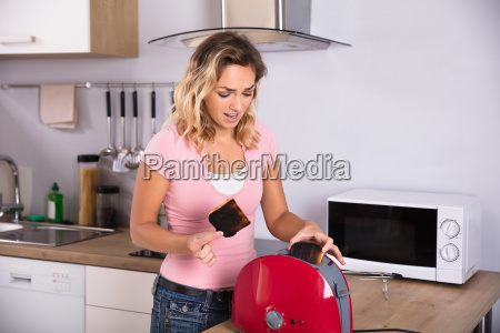 woman, removing, slices, of, burnt, toast - 23597098