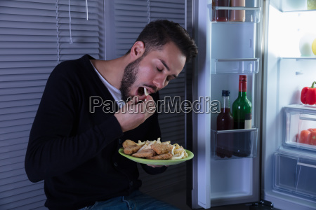 young, man, eating, fried, food - 23597742