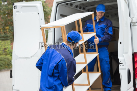 two delivery men unloading shelf from