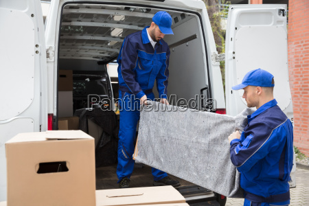 two male worker unloading furniture from