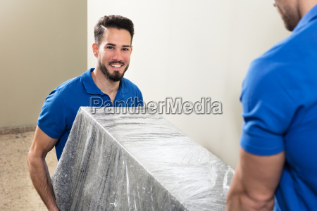 two movers carrying furniture on staircase