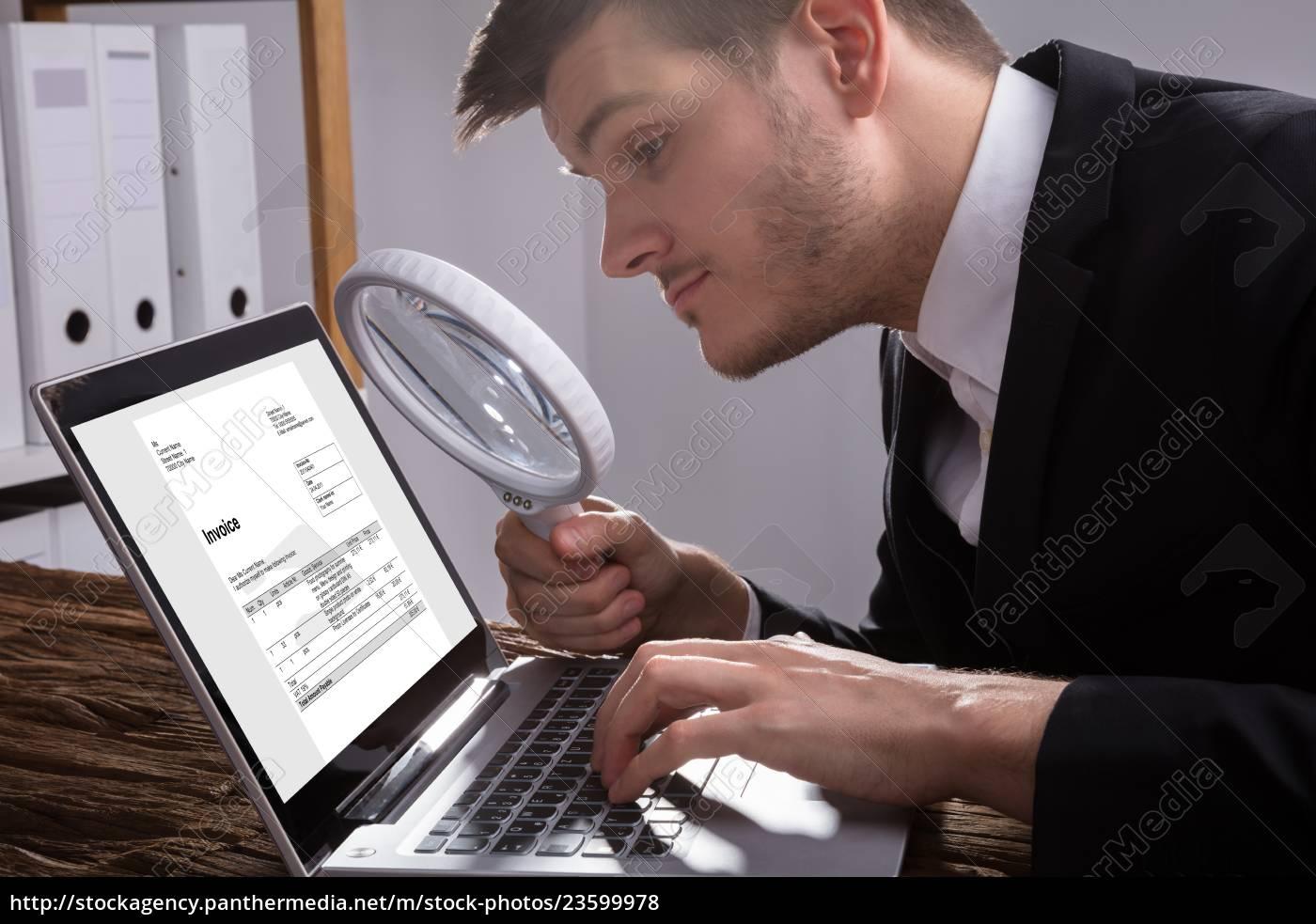 businessman, analyzing, bill, on, laptop - 23599978