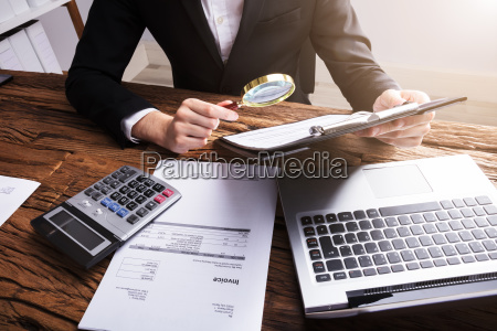 businessperson, analyzing, bill, with, magnifying, glass - 23599990