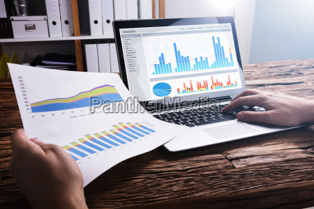 businessperson, analyzing, graph, on, laptop - 23599894