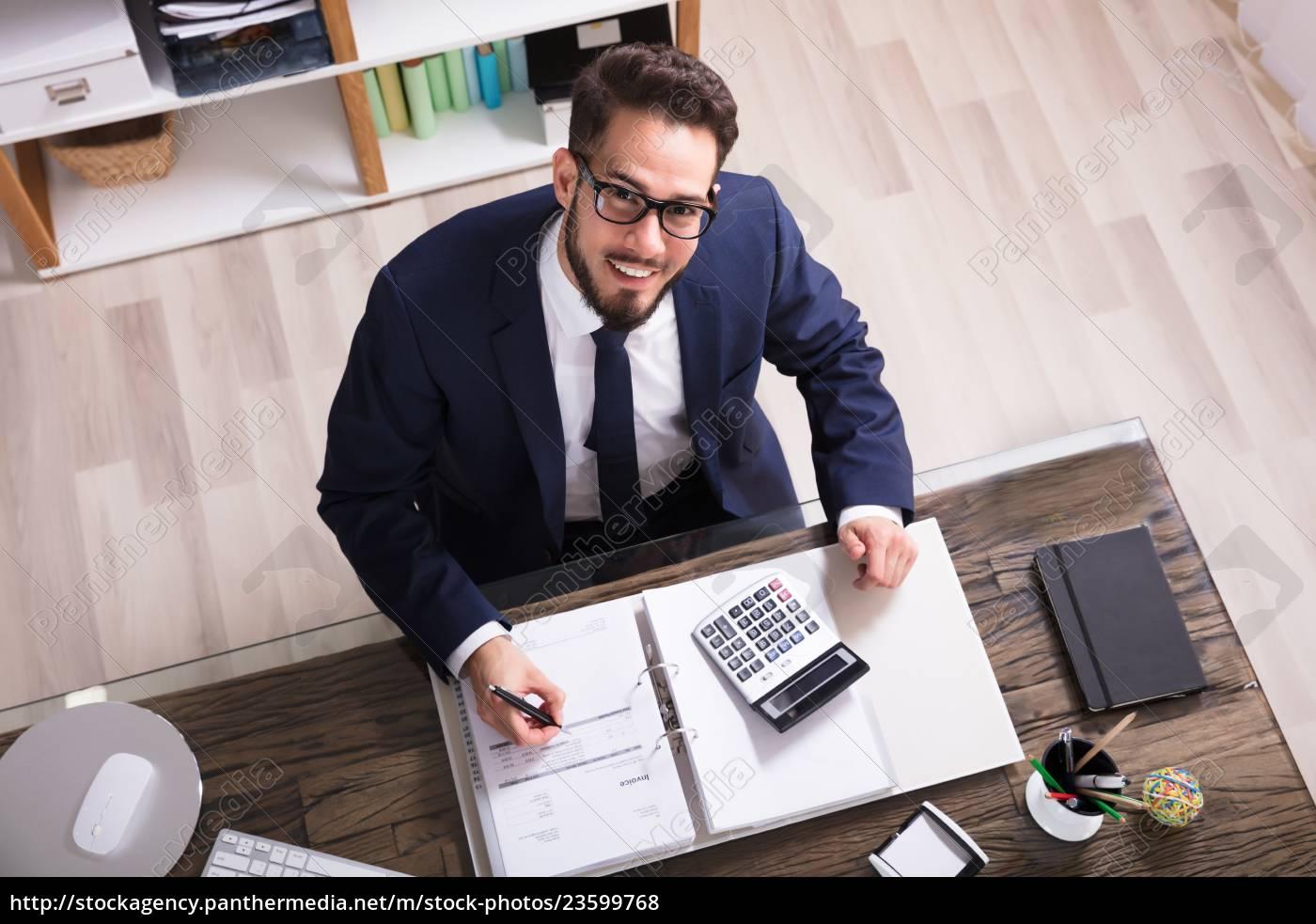 happy, businessman, calculating, bill, in, office - 23599768