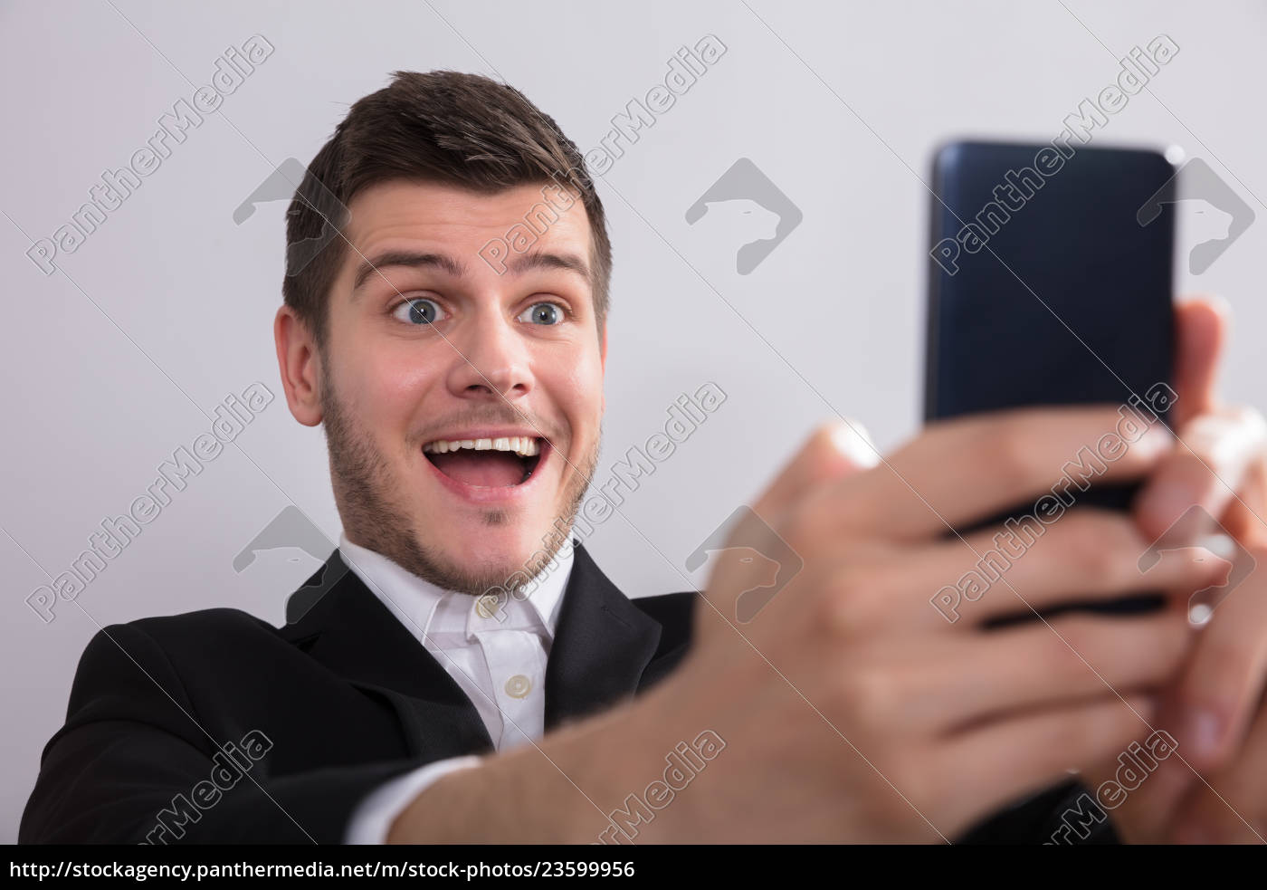 happy, businessman, looking, at, smartphone - 23599956