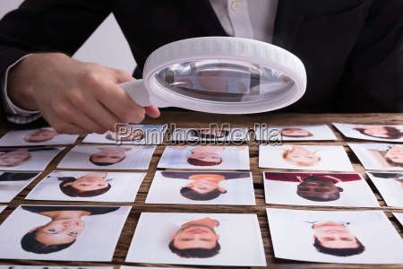 looking, at, candidate's, photograph, with, magnifying - 23599976