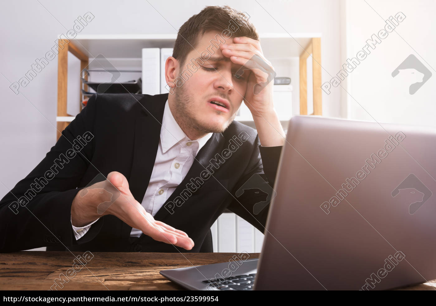 sad, businessman, looking, at, laptop - 23599954