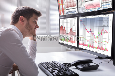 sad, male, operator, looking, at, graphs - 23599940